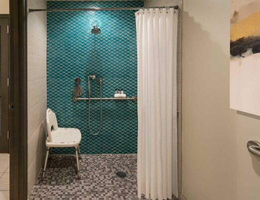 an accessible bathroom with a shower containing a seat