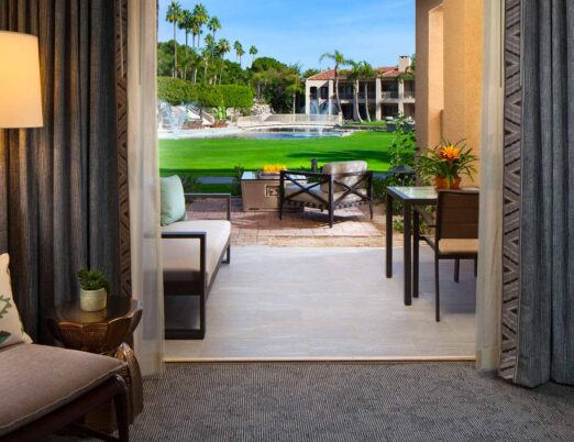 a luxury casita with patio doors opening to an outdoor seating area with a fire table overlooking a lush green lawn