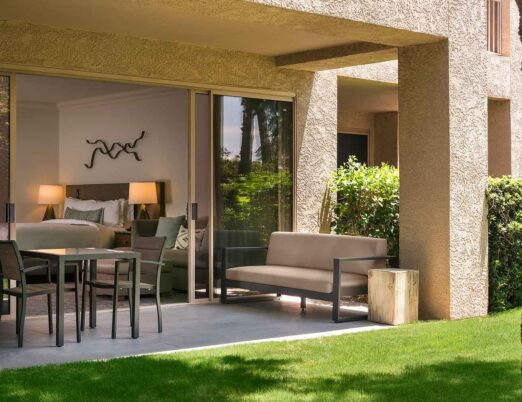 a casita garden patio with outdoor seating and large patio doors opening into the bedroom