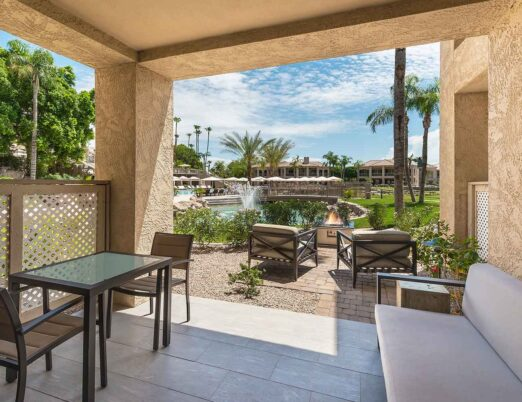 a luxury resort casita patio with covered seating overlooking a lush green lawn and pond with a fountain