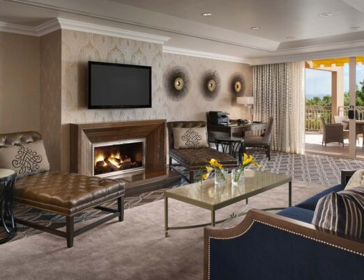 the sitting room in the presidential suite at The Phoenician with daybeds, a fireplace, and patio doors to a private terrace