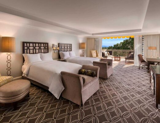 a presidential suite bedroom with two beds and large patio doors opening onto a private terrace