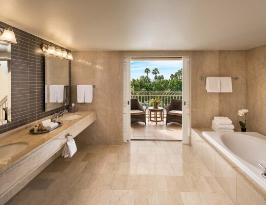 a luxury presidential suite bathroom with deep tub, double vanity, and doors opening onto a private patio