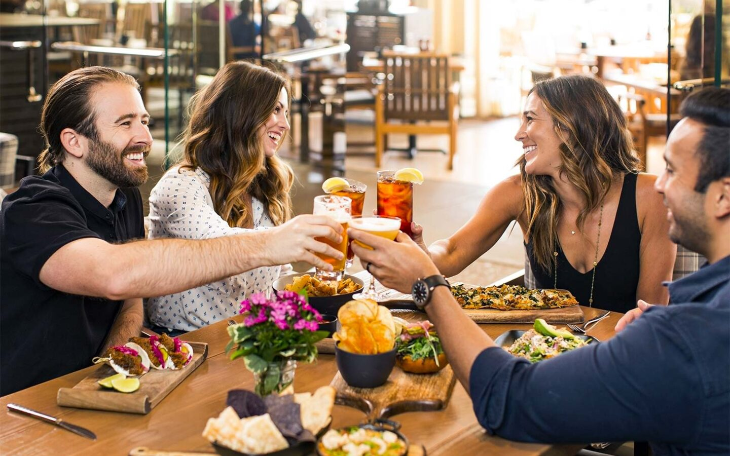 group of four friends sit around restaurant table cheersing glasses over their dinner