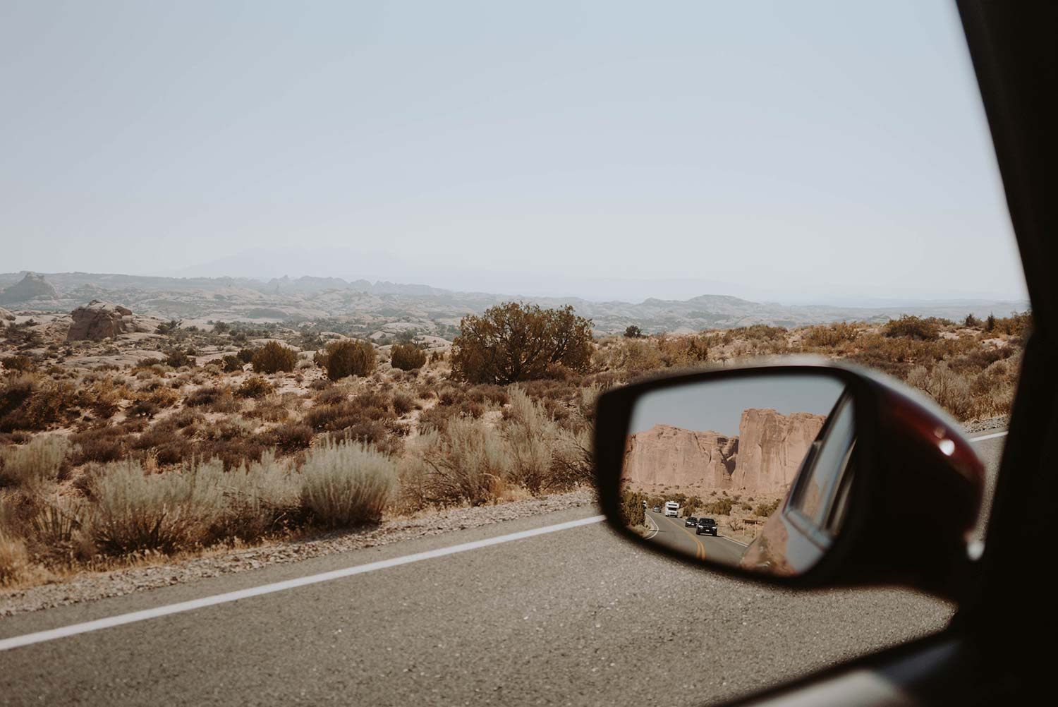view from window passing cactus valley showing rearview mirror of car