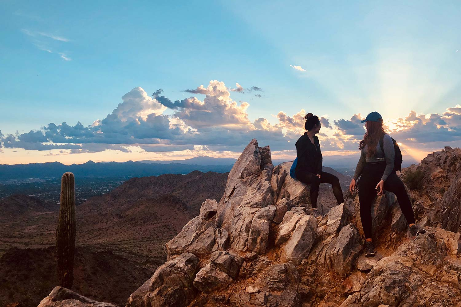 two women sit on rocks at the top of the mountain they've hiked up