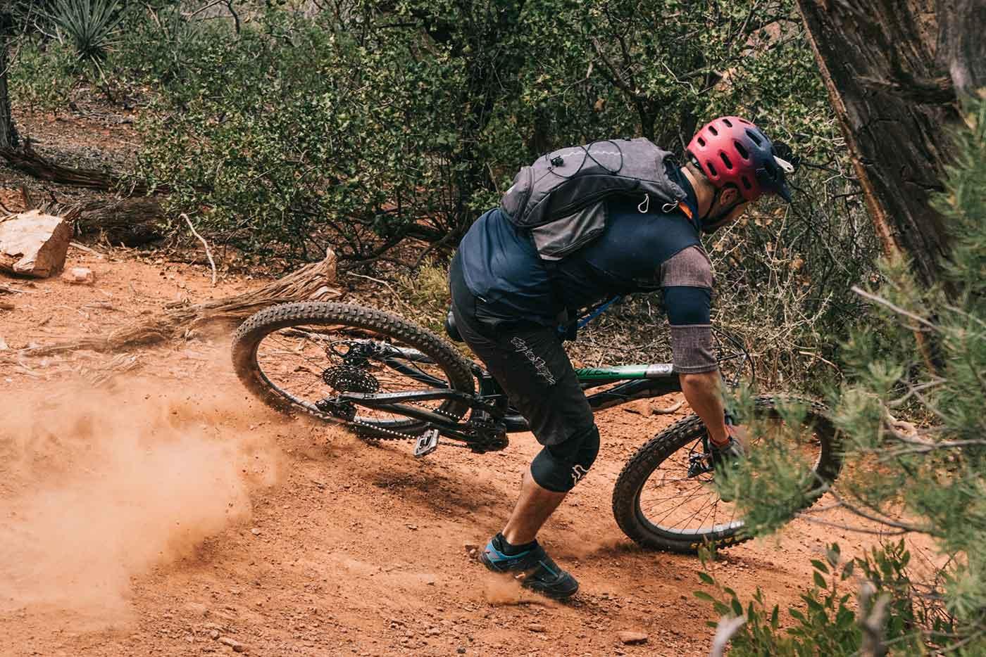 man mountain bikes down a hill