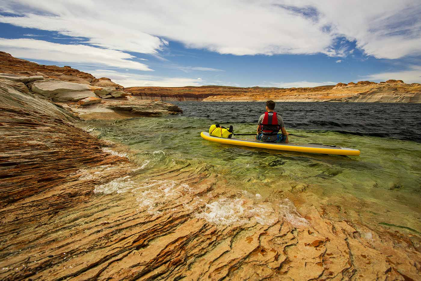 man sits on paddle board taking in the surroundings
