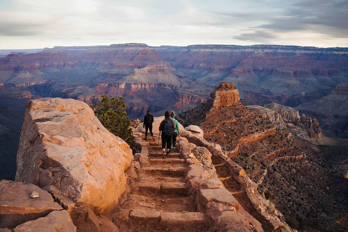 three hikers walk the grand canyon