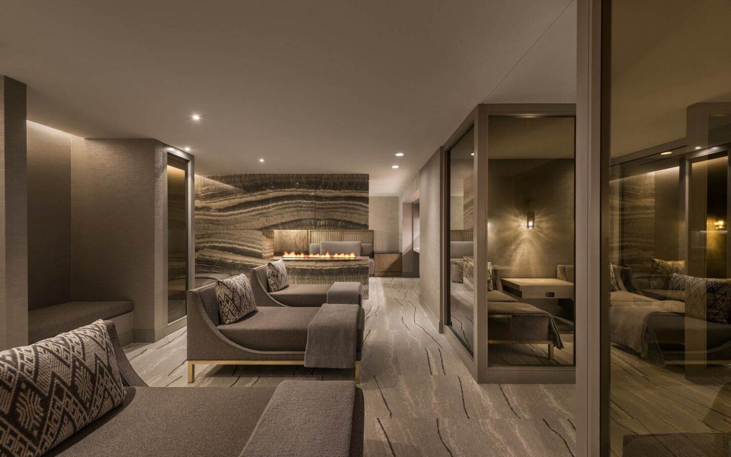 a row of daybeds in a comfortable and dimly lit spa post-treatment room