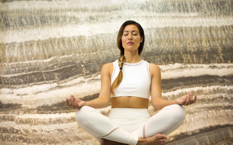 a woman sitting cross legged and meditating