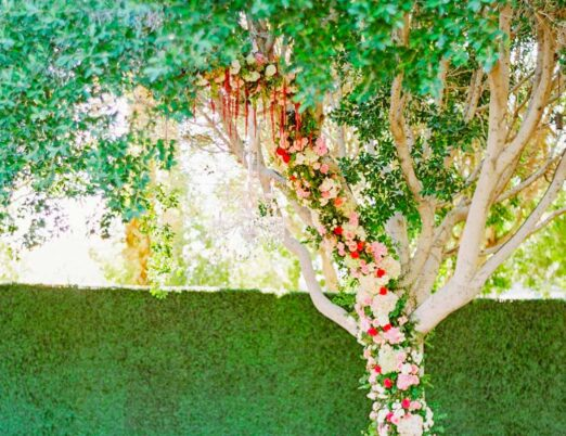outdoor wedding venue with large tree decorated with fresh flowers