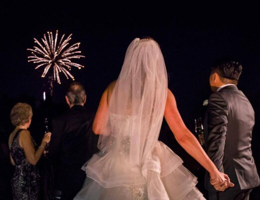 bride and groom watch fireworks in night sky