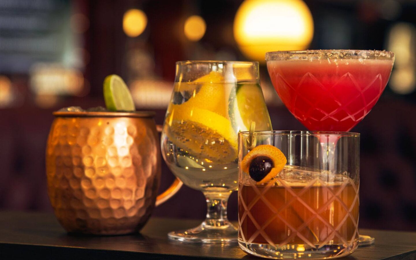 four different cocktails on wooden table