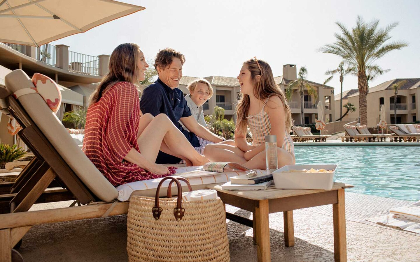 family of four sitting pool side