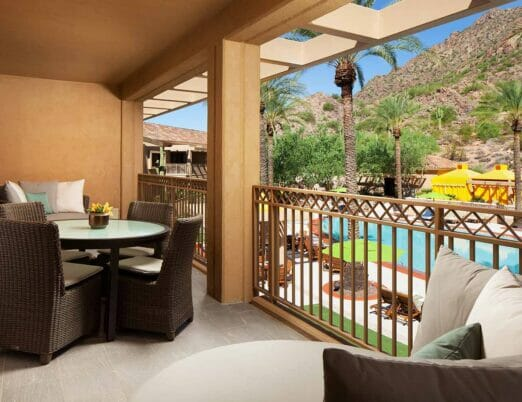 balcony with table wicker chairs and couches overlooking pool
