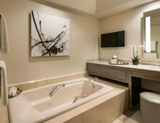 bathroom with bathtub mounted tv and abstract black and white art on wall