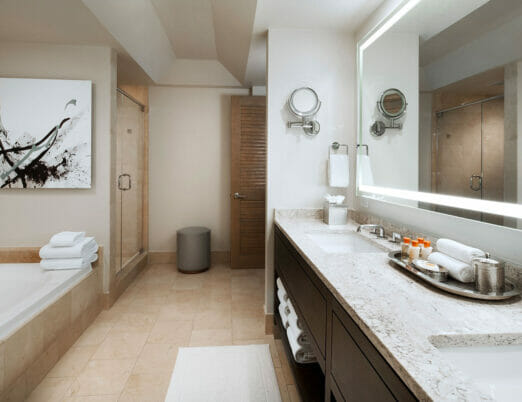 bathroom with double vanity bathtub and shower with black and white abstract art on wall