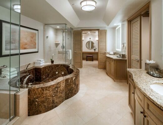 bathroom with large bathtub two glass wall showers and multiple vanities