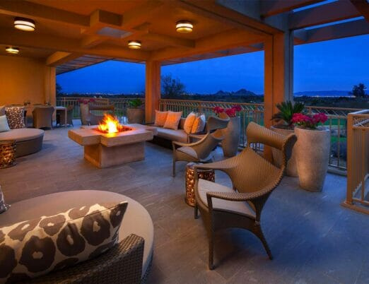 patio with wicker chairs and couches surrounding a fire table