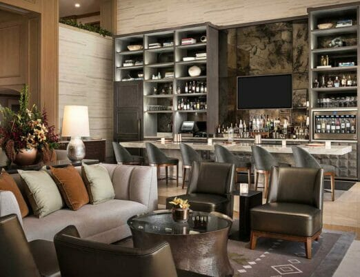 resort lounge with bar and sitting area with leather chairs and grey couch