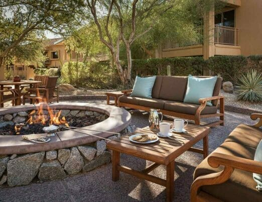 firepit surrounded by wooden tables chairs and couches