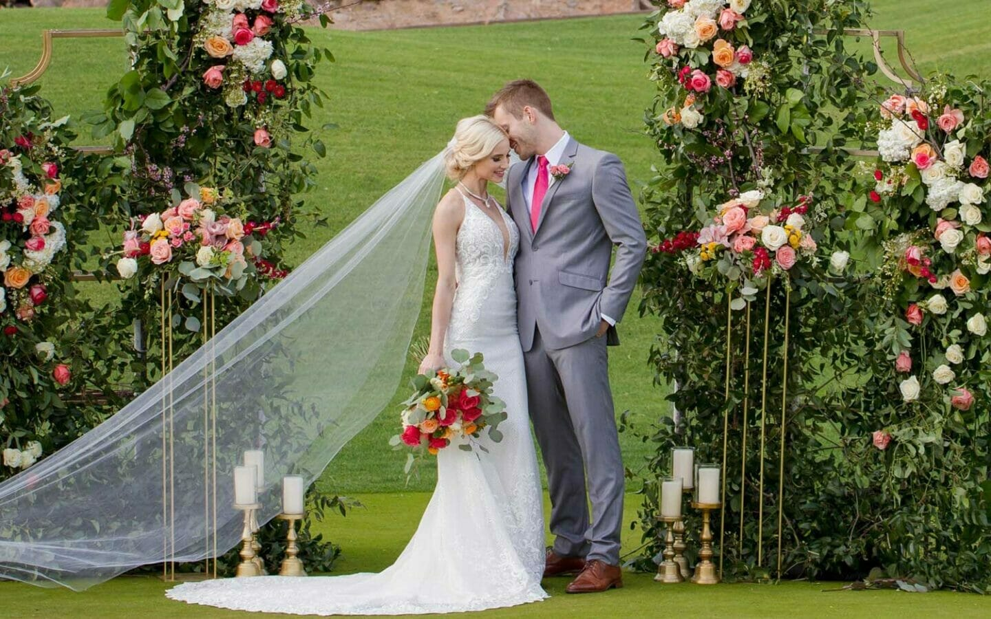 bride and groom on lawn under floral arch