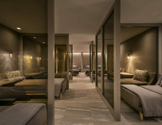rows of daybeds, separated by glass panes, in a comfortable and dimly lit spa post-treatment room