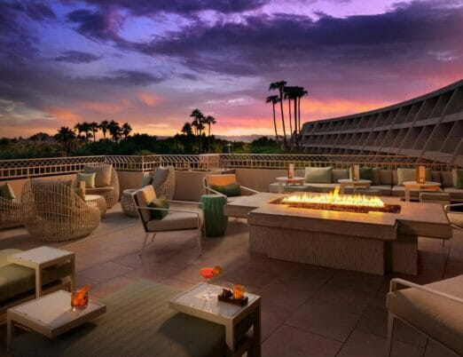 Thirsty Camel Patio at dusk with multiple seating areas and a large fire table in the middle