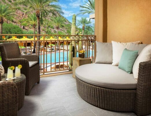 suite balcony with two wicker chairs and large wicker couch with pillows overlooking resort pool
