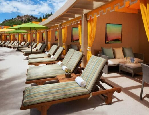 line of cabanas with yellow curtains long lounge chairs and umbrellas in front of them