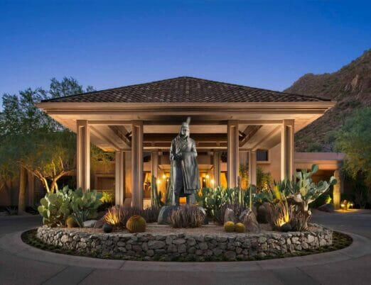 resort exterior entrance with silver statue at center of roundabout