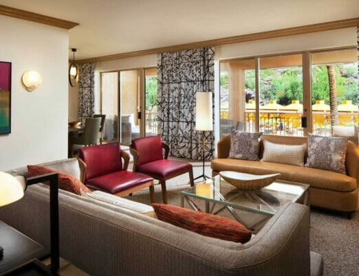 suite living room with two couches two red chairs and glass table in the center