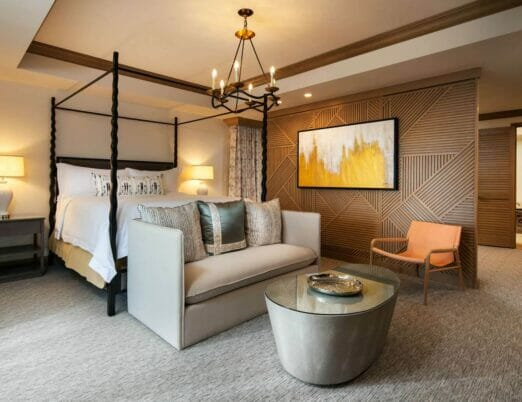 suite room featuring bed with black framing grey couch and table with glass top