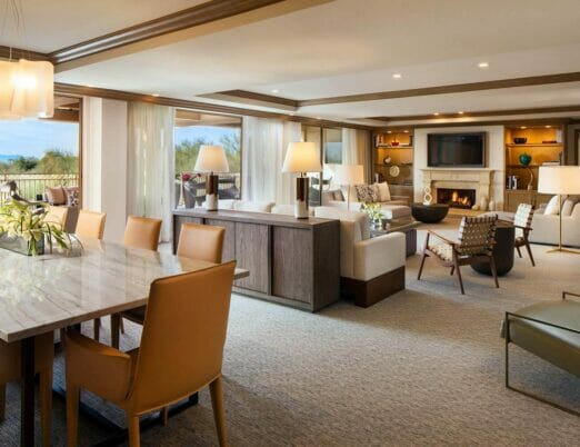 large suite room with dining table in the foreground and couches and tv in the background