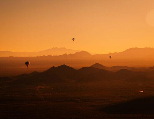 three hot air balloons flying over desert at sunset