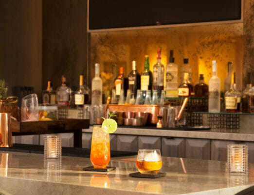 bar counter with drink in tall glass and drink in small glass with various bottles on the shelf in the background