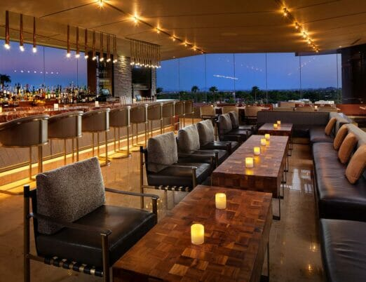 JG Steakhouse bar with high chairs lining the bar and floor-to-ceiling windows looking out on the resort