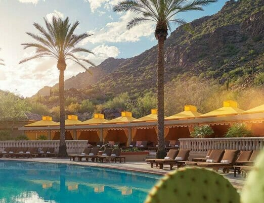 palm trees lining pool with yellow cabanas and mountain in the background