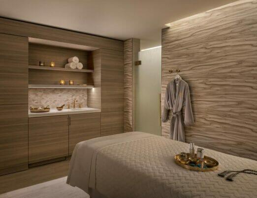 spa treatment room with long bed and robe hanging on wall