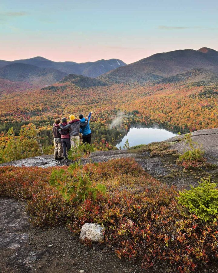 group of four friends stand on mountain peak during fall and pointing to view