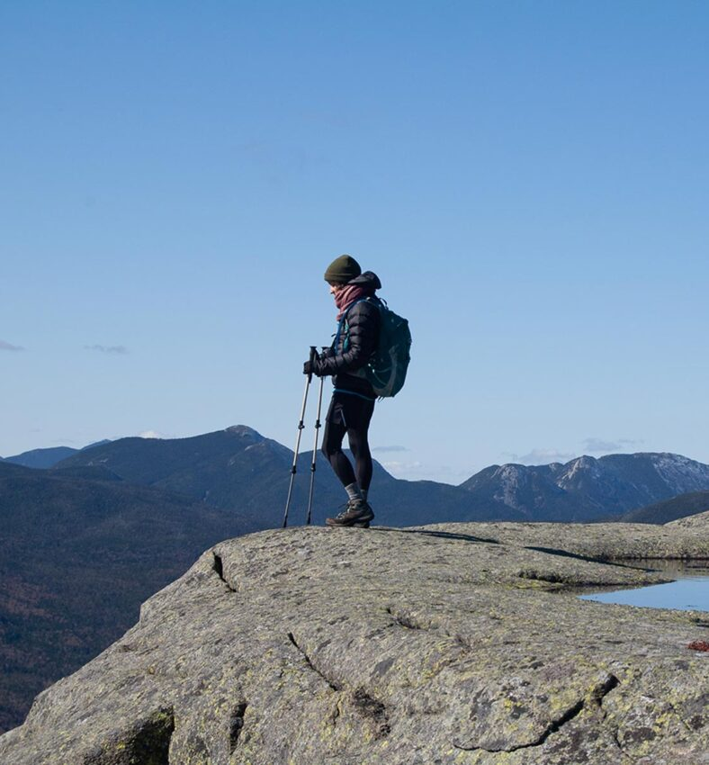 woman stands on rocks edge to see the view off of the tall mountain just hiked while wearing warm outdoor attire and backpack