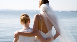 back view of a bride and girl wearing white dresses overlooking a lake