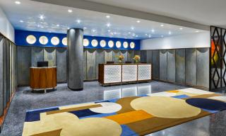 front reception area with modern interior design, bright lights, wooden desks, colourful carpet with circle and square pattern
