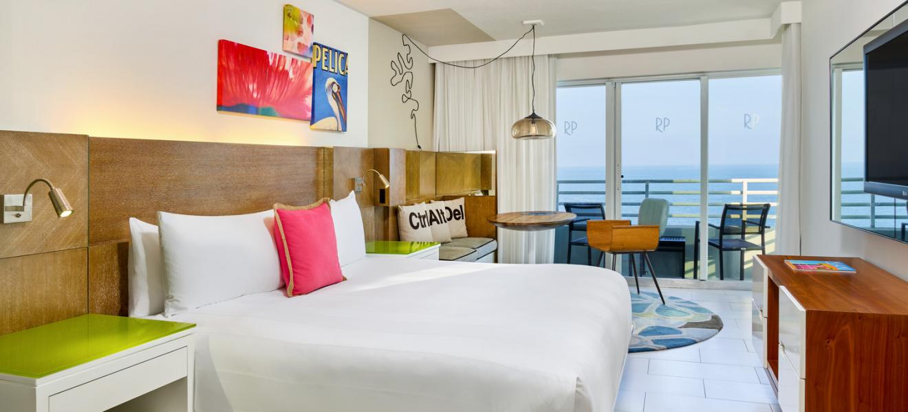 ocean view guest room with a king bed paintings on the wall and large ocean view window with balcony