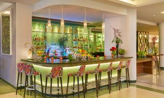 tropical bar with green lights surrounded by flower patterned stools and bottles of alcohol on shelves in the back