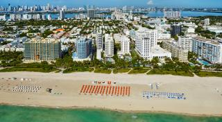 birds eye view of multiple beachfront resorts bordered by palm trees at a beach filled with chairs and umbrellas