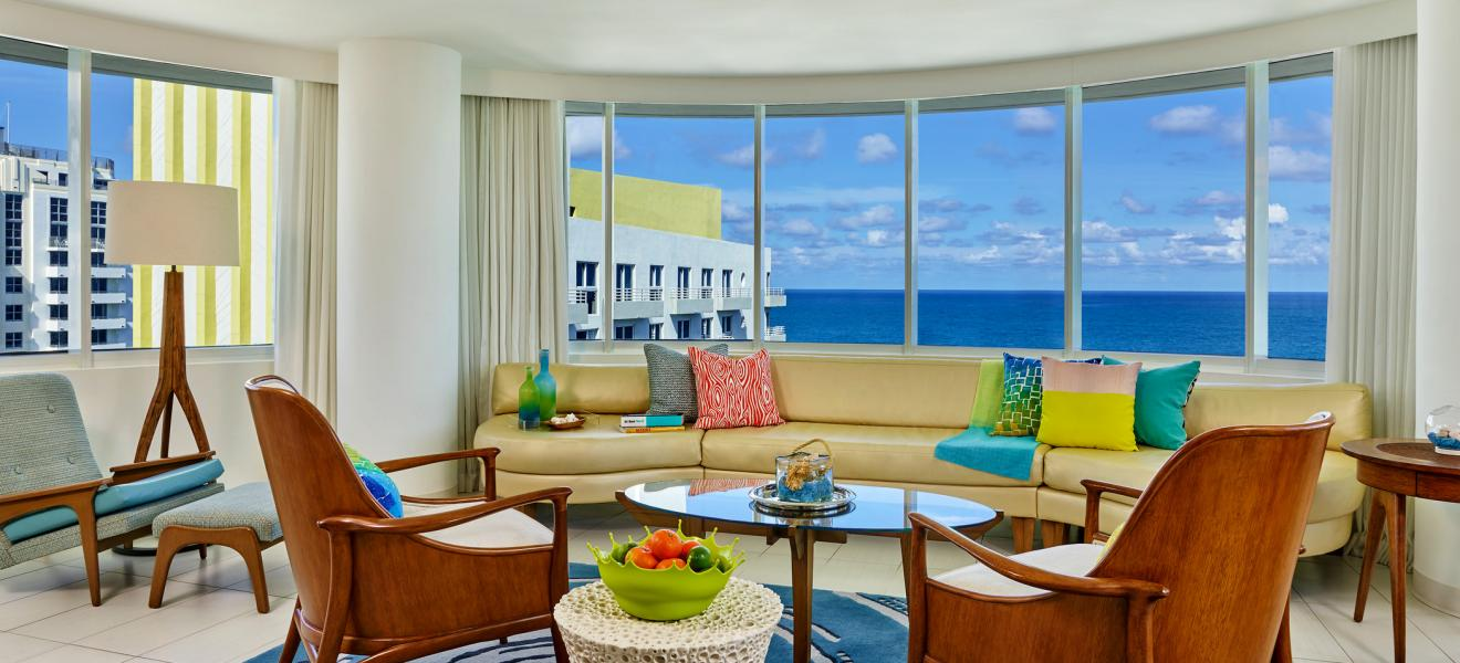 ocean view suite with long fabric couch colourful pillows wooden furniture and a large ocean view windows