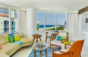 ocean view suite with large windows fabric couch colourful pillows wooden furniture overlooking beach