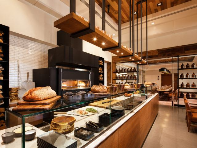 large modern bakery with a wood fired oven behind a long counter top with full length vitrine and fresh rustic breads across the top.